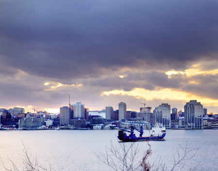 December 11, 2013: Halifax, Nova Scotia- a cargo vessel sits in the Halifax Harbour with the city behind it