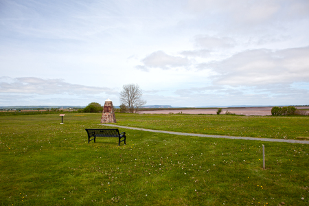 A stone monument marks the settlement spot and deportation area of many Acadian settlers in the 1700s, with Cape Blomidon in background