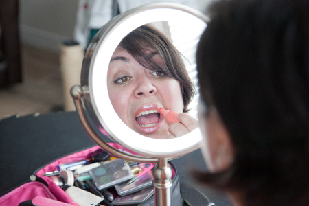 Woman in mirror puts on a shiny pink lip gloss
