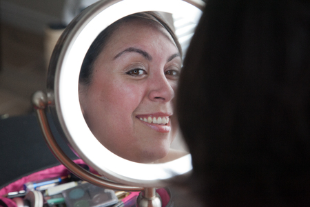 Beautiful woman smiles at her reflection in a lit mirror 스톡 콘텐츠