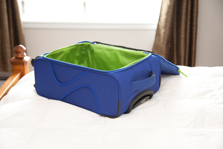 A blue and green unzipped suitcase sits on a bed, ready to be packed for an adventure Stock Photo