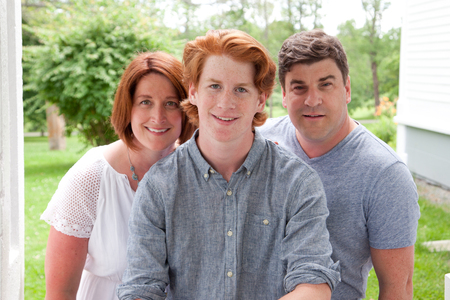 A handsome ginger red head boy with his proud smiling parents Stock Photo
