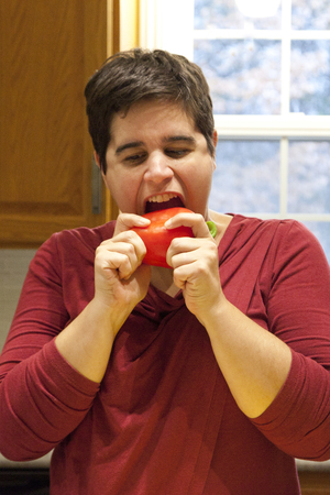 opening mouth to take a big bite of a red bell pepper in the kitchen Stock Photo