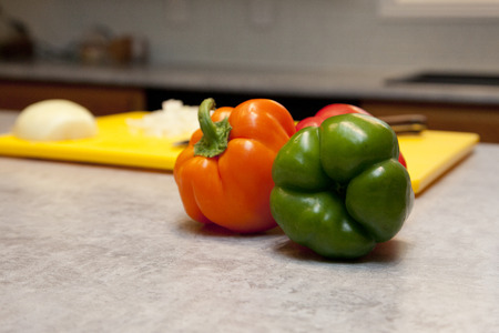 Red and green bell peppers next to a cutting board in the kitchen with copy space