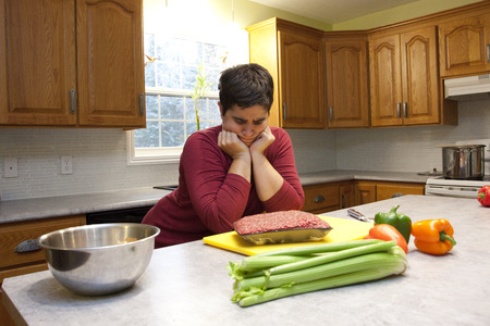 Woman looks down at package of raw meat unsure about what to do in kitchen Stock Photo