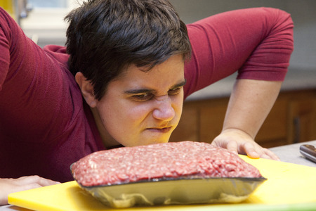 Woman glares angrily at a package of red meat