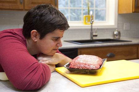 Woman looks at package of red meat and considers whether to eat it Stock Photo