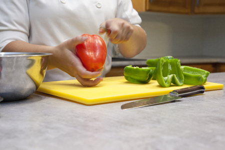 Close up of hands slicing a red bell pepper on a cutting board in the kitchen Stock Photo