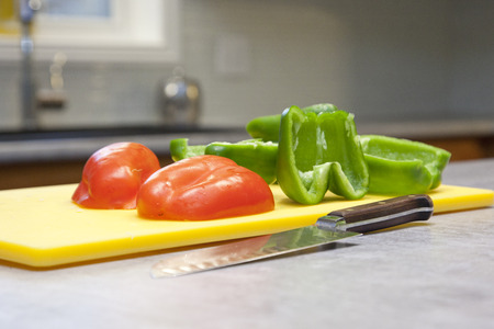Green and red peppers on a cutting board with a knife