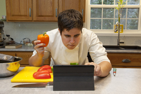 Chef in the kitchen with vegetables looks at their tablet to get a recipe