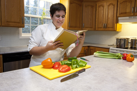 Woman in a chefs outfit in their kitchen with cut peppers smiles as they decide on a recipe