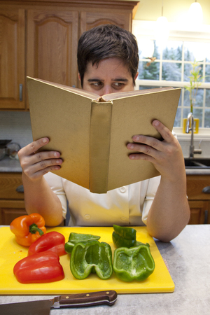 Person in chefs outfit holds a cookbook and reads instructions, with cut peppers in foreground Stock Photo