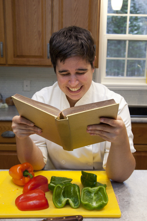In the kitchen with cut vegetables and a cutting board, a chef smiles as they read a cookbook Stock Photo