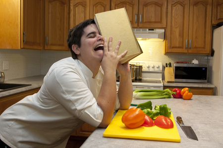 Person crying in the kitchen, sobbing into their cookbook with vegetables in the foreground