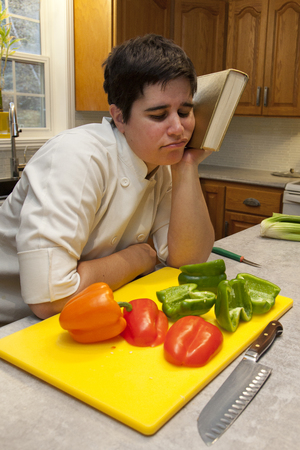 Dressed in a chefs outfit a person leans their head against a cookbook in despair with vegetables in the foreground
