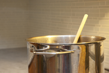 A large metal vat of soup or stew on the stove with a wooden handle in the kitchen