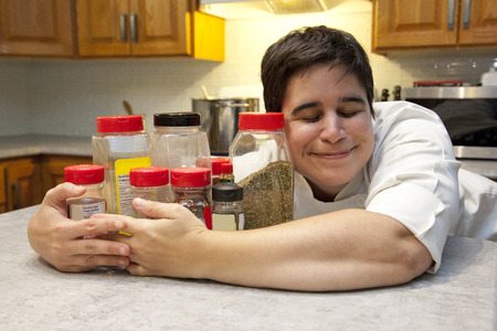 A happy chef holds her collection of spices and seasoning close with a happy expression