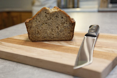 On a wooden cutting board, a sharp knife has sliced homemade baked banana bread Stock Photo