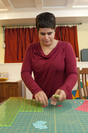Woman in her sewing room cutting small squares of fabric Stock Photo
