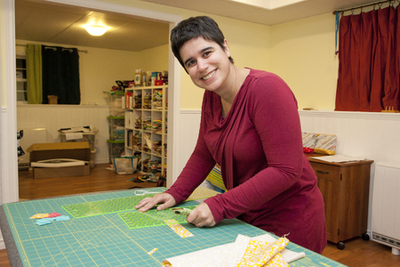Smiling person working with a fabric grid and cutter in their craft room Stock Photo