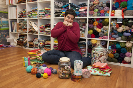 Person surrounded by fabric, yarn, looking gleeful and excited to create Stock Photo