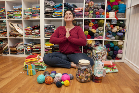 Person sits in a meditative position in their craft sewing space surrounded by creative colour
