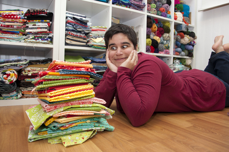 Person laying in front of a stack of colorful fabric looking wide eyed and excited
