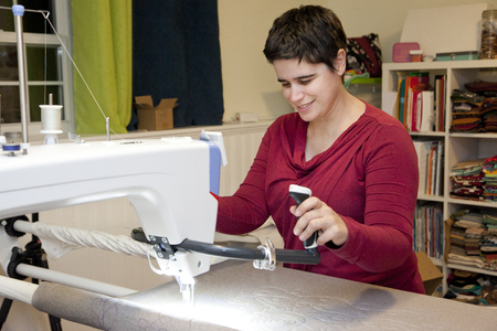Person in their sewing studio embriodering with a long arm machine