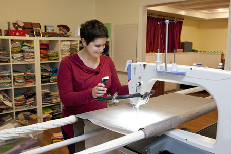 Smiling person works on a long arm sewing machine in her studio Stock Photo