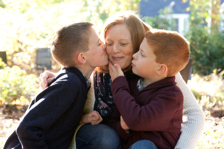 A red haired mother smiles peacefully as her two sons give her a gentle affectionate kiss