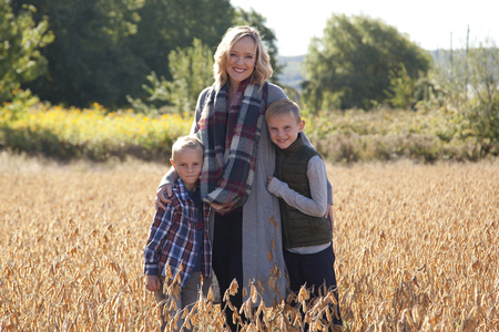 A beautiful smiling mom puts her arms around her two sweet sons, outside in a field