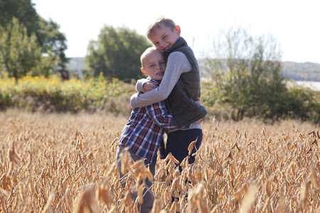 Two blond brothers hugging outside in a field on a sunny autumn day