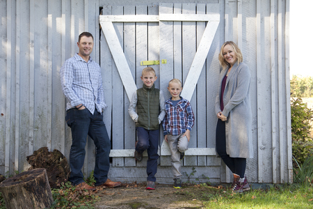 Family of four leans in a relaxed portrait against their grey shed Stock Photo - 113086111