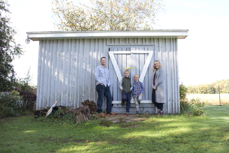 A beautiful blond family of four leans casually against their grey shed outside on a fall day Stock Photo