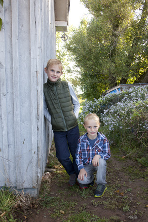 Two cute blond children lean casually against a shed or barn in autumn dress