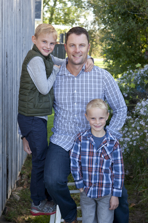 Handsome blond man with a great smile and his two cute sons outside Stock Photo - 113086120
