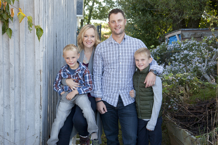 Stunning blond mom and dad outside for a portrait with their two sweet boys
