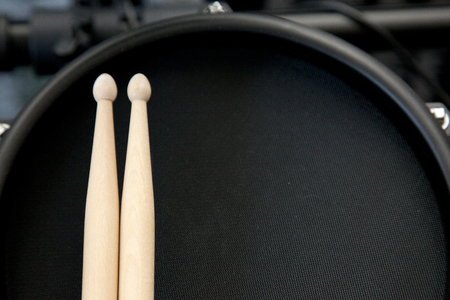 Looking down on a black electronic drum with two sticks ready to be played Stock Photo - 113086123
