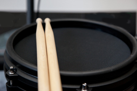 Black electronic drum with two wooden sticks resting with copy space to the side