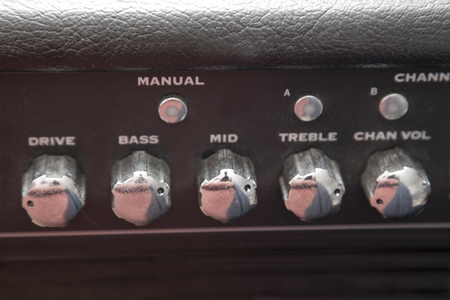 Dials that set the range and channel for a guitar amplifier Stock Photo - 113086142