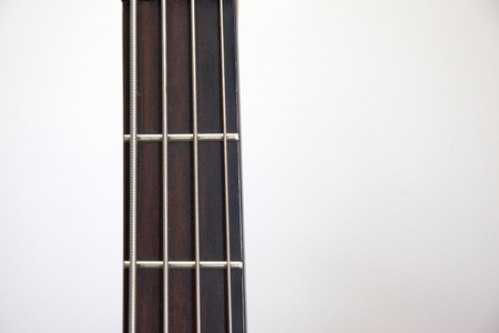 The neck of a bass guitar against white copy space Stock Photo - 113086148