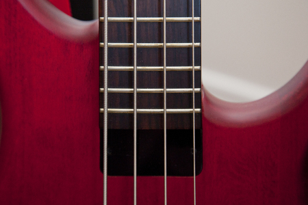 Bass guitar strings and frets on a beautiful red instrument