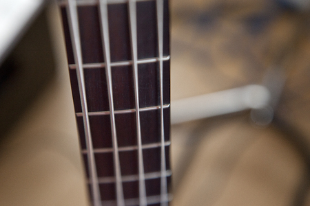 Soft focus on the wooden frets and metal strings of a bass guitar Stock Photo