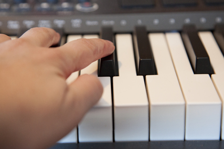 Fingers playing on a digital media keyboard or piano