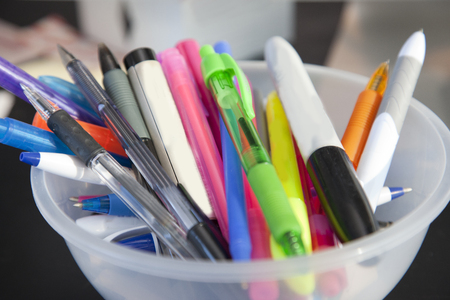 Pens, highlighters and permanent markers fill a bowl of writing utensils at home or office Stock Photo - 113086262
