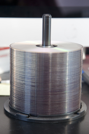 Tower of blank CDs or DVDs in front of a computer Stock Photo - 113086195