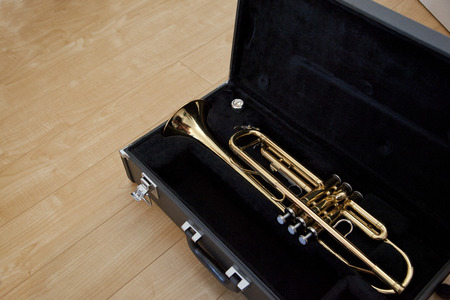 Gold trumpet in a black case on the floor, with copy space