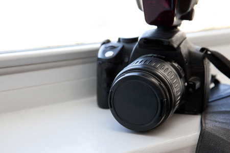Camera and flash and strap in the window with copy space