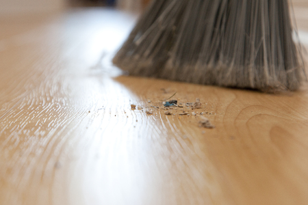 Close up of dirt and sweepings on the floor beside a broom Stock Photo - 113086331