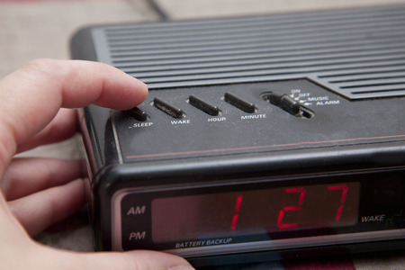 Pushing the sleep or snooze button on an old analog alarm clock Stock Photo - 113086334
